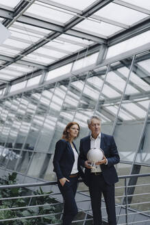 Businessman and businesswoman holding globe in modern office building - JOSF04162