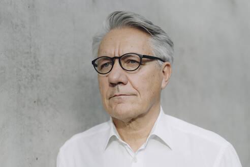 Portrait of a pensive senior businessman at a concrete wall - JOSF04168