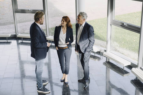 Business people talking at the window in modern office building - JOSF04171