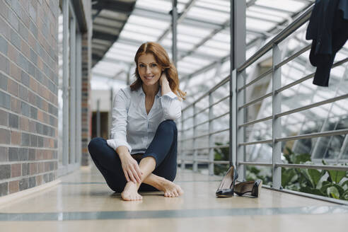 Portrait of smiling businesswoman sitting on the floor in a modern office - JOSF04192