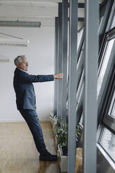 Senior businessman holding girder in office - JOSF04195