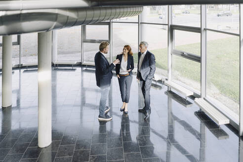 Business people talking at the window in modern office building - JOSF04207