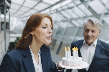 Businessman and businesswoman celebrating birthday in office with fake birthday cake - JOSF04216