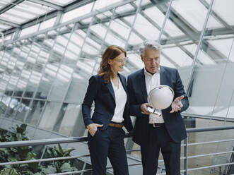 Businessman and businesswoman looking at globe in modern office building - JOSF04225