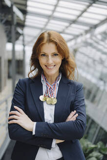 Portait of a smiling businesswoman wearing medals around her neck in office - JOSF04234