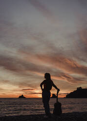 Silhouette of woman with guitar standing on the beach at sunset, Almunecar, Spain - LJF01215
