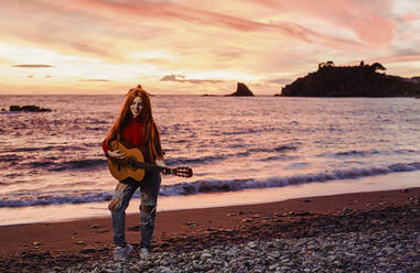 Redheaded young woman playing guitar on the beach at sunset, Almunecar, Spain - LJF01218