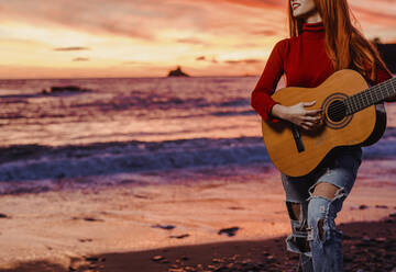Crop view of young woman playing guitar on the beach at sunset, Almunecar, Spain - LJF01221