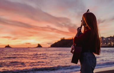 Young woman with guitar standing on the beach at sunset looking at the sea, Almunecar, Spain - LJF01224