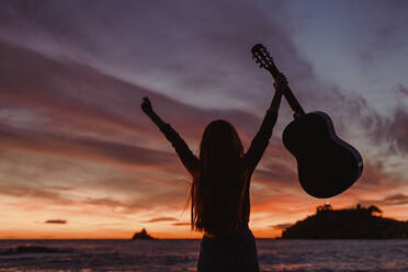 Silhouette of woman with guitar standing on the beach at sunset, Almunecar, Spain - LJF01227