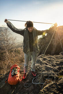 Female climber with rope standing on Battert rock at sunset, Baden-Baden, Germany - MSUF00110