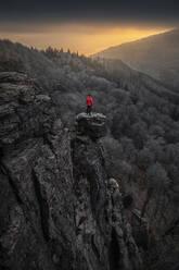 Man standing on rock needle at sunrise at Battert rock, Baden-Baden, Germany - MSUF00116