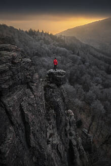 Man standing on rock needle at sunrise at Battert rock, Baden-Baden, Germany - MSUF00116