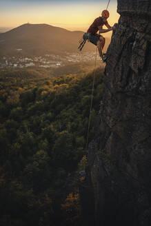 Man climbing at Battert rock at sunset, Baden-Baden, Germany - MSUF00125