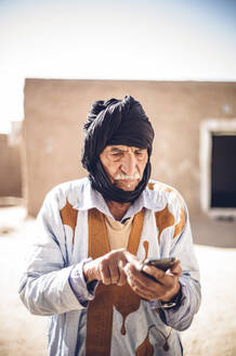 Senior man using cell phone in Smara refugee camp, Tindouf, Algeria - OCMF00961
