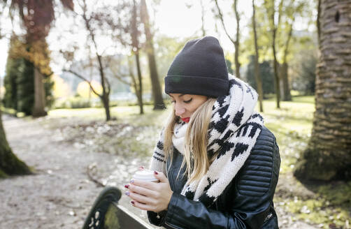 Beautiful blond woman having a take away coffee in a park - MGOF04231