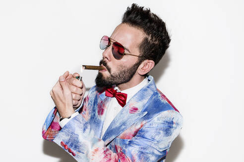 Cool and stylish man wearing a colorful suit and sunglasses lighting a cigar - LOTF00082
