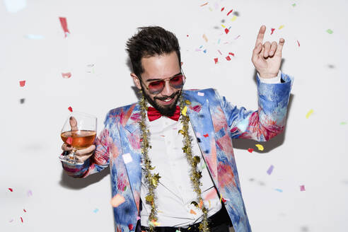 Cool and stylish man wearing a colorful suit and sunglasses dancing at a party - LOTF00085