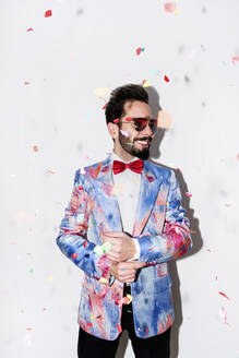 Cool and stylish man wearing a colorful suit and sunglasses smiling at a party surrounded by confetti - LOTF00088
