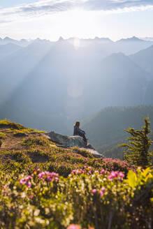 Female hiker enjoying sun on peak, Winchester Mountain, North Cascades, Washington - ISF23516