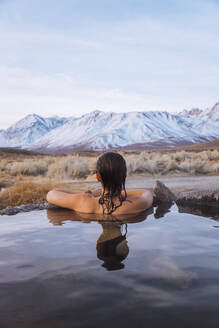 Woman enjoying hot spring in cold winter, Mammoth Lakes  Hot Spring, California, USA - ISF23534