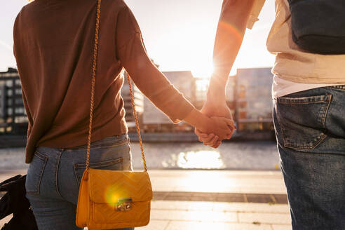 Midsection of couple holding hands while exploring city - MASF16023