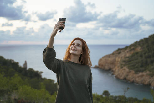 Redheaded young woman taking a selfie at the coast, Ibiza, Spain - AFVF04837