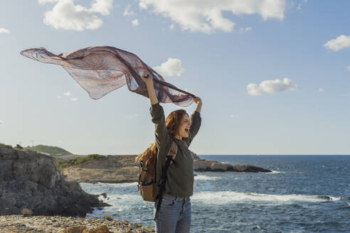 Happy redheaded young woman holding a cloth at the coast, Ibiza, Spain - AFVF04846