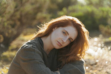 Portrait of beautiful redheaded young woman outdoors at sunset - AFVF04849