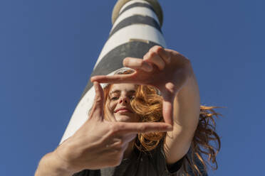 Portrait of redheaded young woman at a lighthouse - AFVF04852