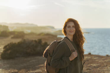 Portrait of redheaded young woman at the coast at sunset, Ibiza, Spain - AFVF04855