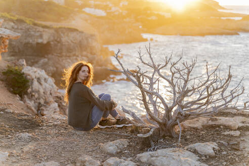 Redheaded young woman sitting at the coast at sunset, Ibiza, Spain - AFVF04861