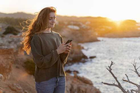 Redheaded young woman using cell phone at the coast at sunset, Ibiza, Spain - AFVF04864