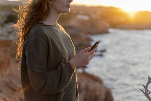 Redheaded young woman with cell phone at the coast at sunset, Ibiza, Spain - AFVF04867