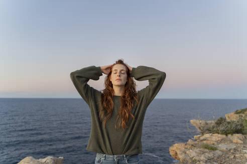 Redheaded young woman at the coast at sunset, Ibiza, Spain - AFVF04873