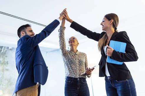 Business people high fiving in office - JSRF00753