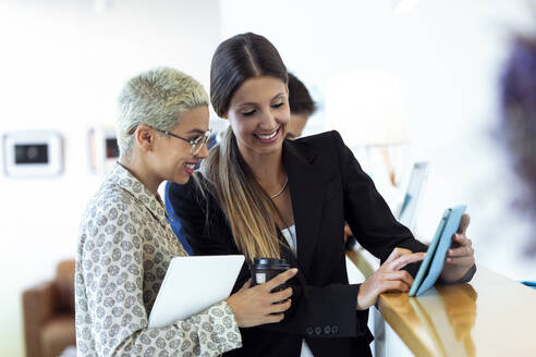 Two smiling businesswomen with takeaway coffee and tablet at reception desk - JSRF00768
