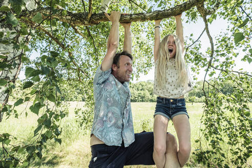 Father and daughter hanging on a branch of a birch tree - WFF00240