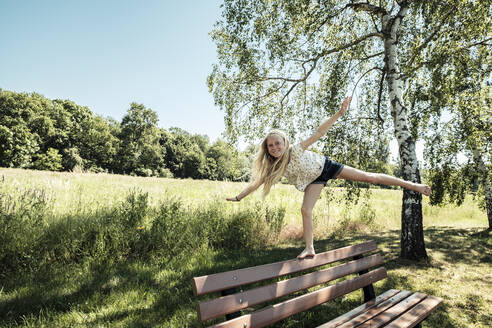 Girl balancing on a bench in park - WFF00246