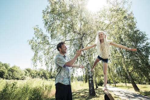 Father helping daughter balancing on a bench in park - WFF00249