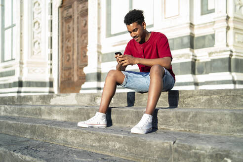Young man sitting on outdoor stairs checking his smartphone, Florence, Italy - FBAF01138