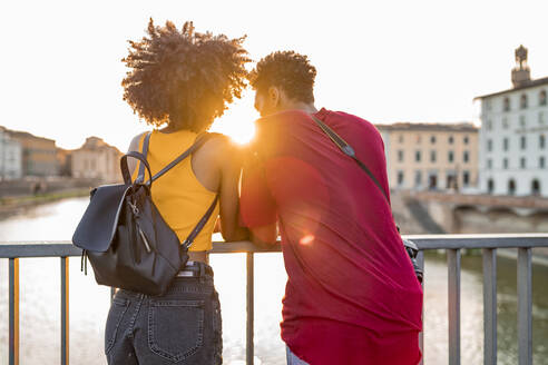 Young tourist couple standing on a bridge above river Arno at sunset, Florence, Italy - FBAF01156