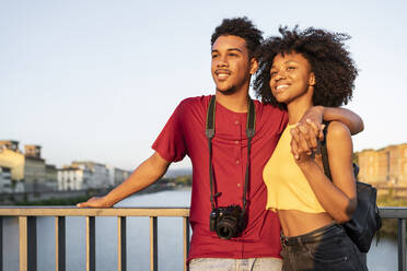 Happy young tourist couple on a bridge above river Arno at sunset, Florence, Italy - FBAF01162