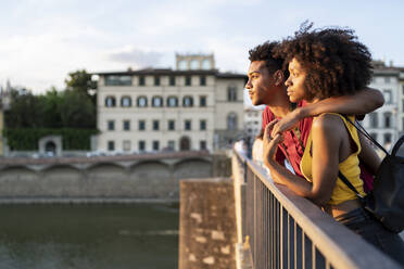 Young tourist couple on a bridge above river Arno at sunset, Florence, Italy - FBAF01165