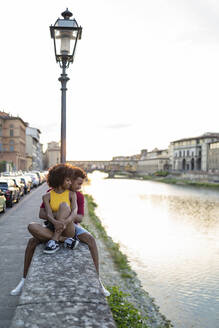 Affectionate young tourist couple sitting on a wall at river Arno at sunset, Florence, Italy - FBAF01168