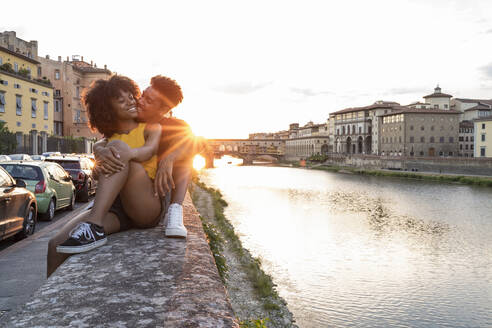 Affectionate young tourist couple sitting on a wall at river Arno at sunset, Florence, Italy - FBAF01171