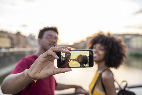 Young tourist couple taking a selfie on a bridge above river Arno at sunset, Florence, Italy - FBAF01183