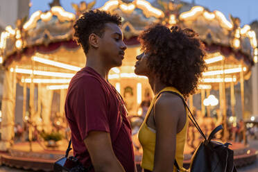 Affectionate young tourist couple at an illuminated carousel in the city at dusk, Florence, Italy - FBAF01186
