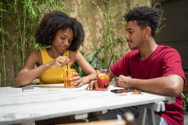 Young couple having a drink at an outdoor bar - FBAF01192