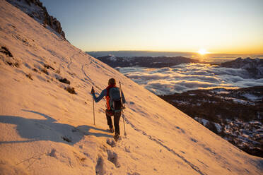 Mountaineer on the mountainside during sunrise, Orobie Alps, Lecco, Italy - MCVF00162